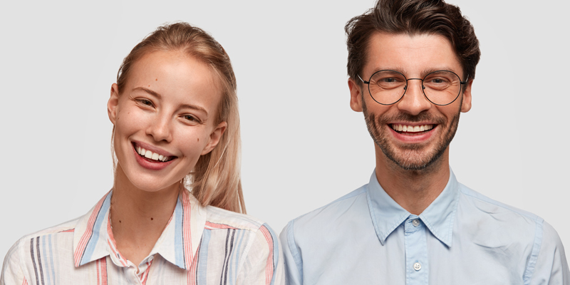 Two UX designers standing side by side, smiling