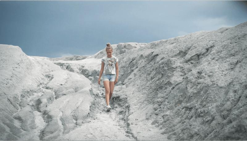 Mädchen spaziert durch trockene Landschaft