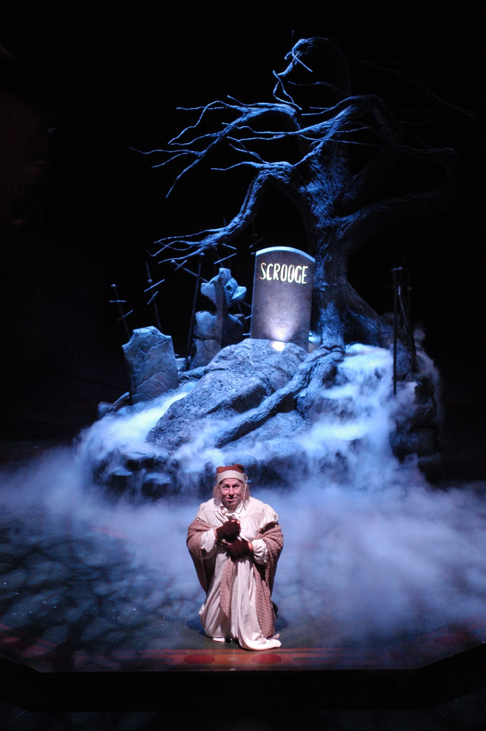 Man in nightclothes kneels on smoke-filled stage in front of his gravestone under a tree.