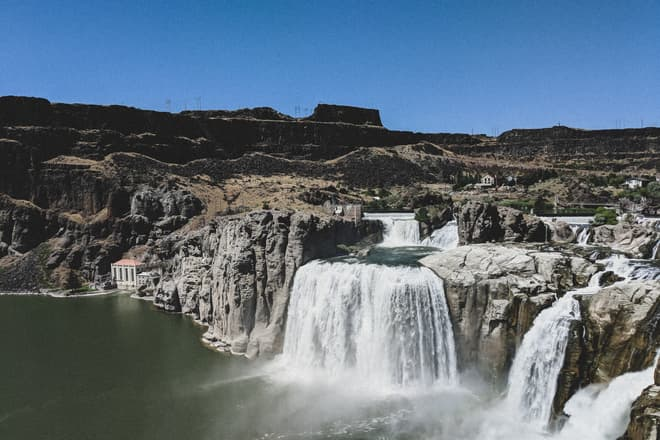 Multiple waterfalls plunge over a cliff of gray volcanic rock into a steep canyon whose sheer walls are composed of much darker basalt.