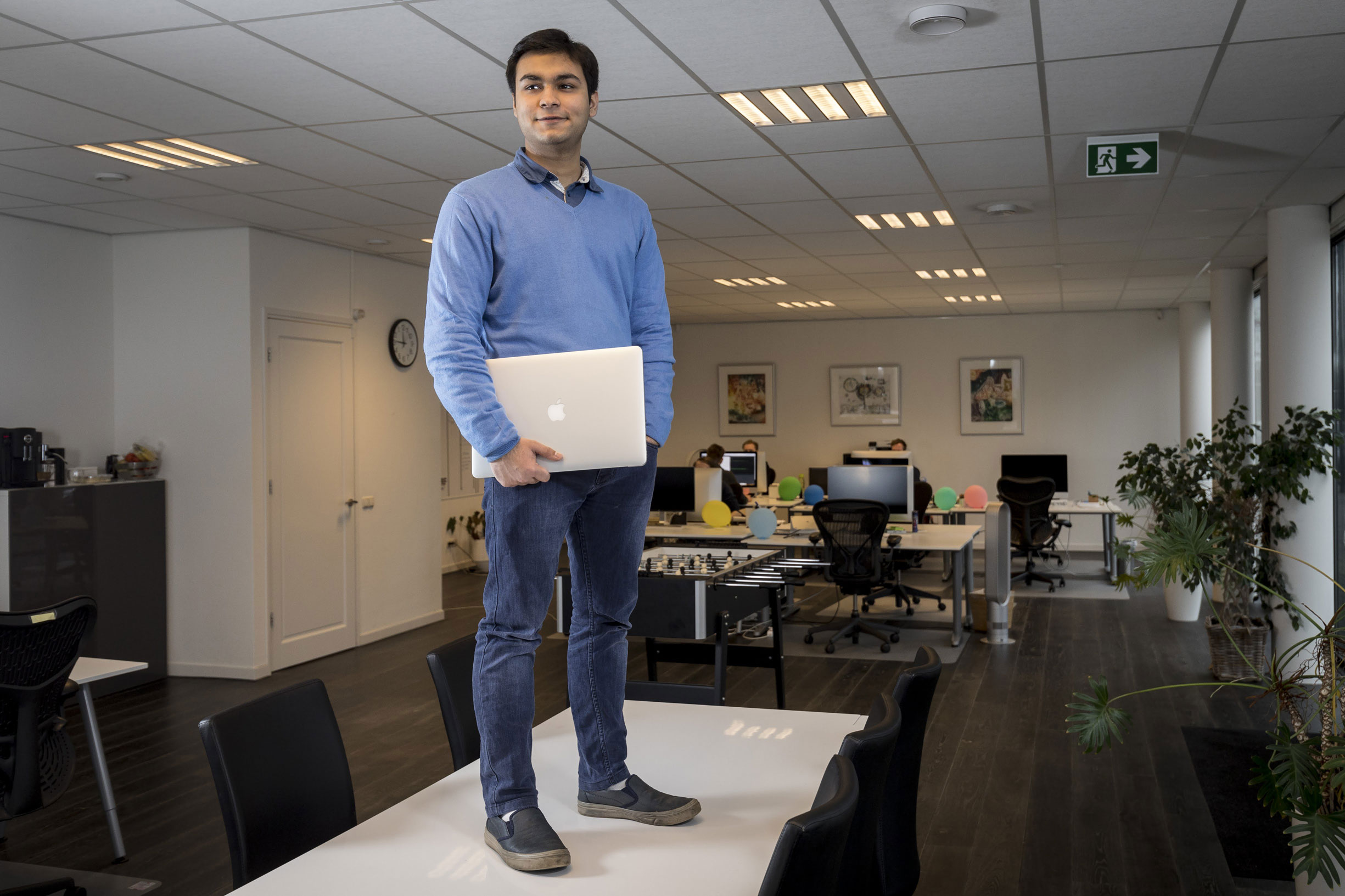 Anand Chowdhary standing on a desk in his office