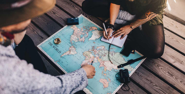 Ein junges Paar nutzt eine Weltkarte, um eine Reise zu planen - Wünsche erfüllen durch gezielten Vermögensaufbau