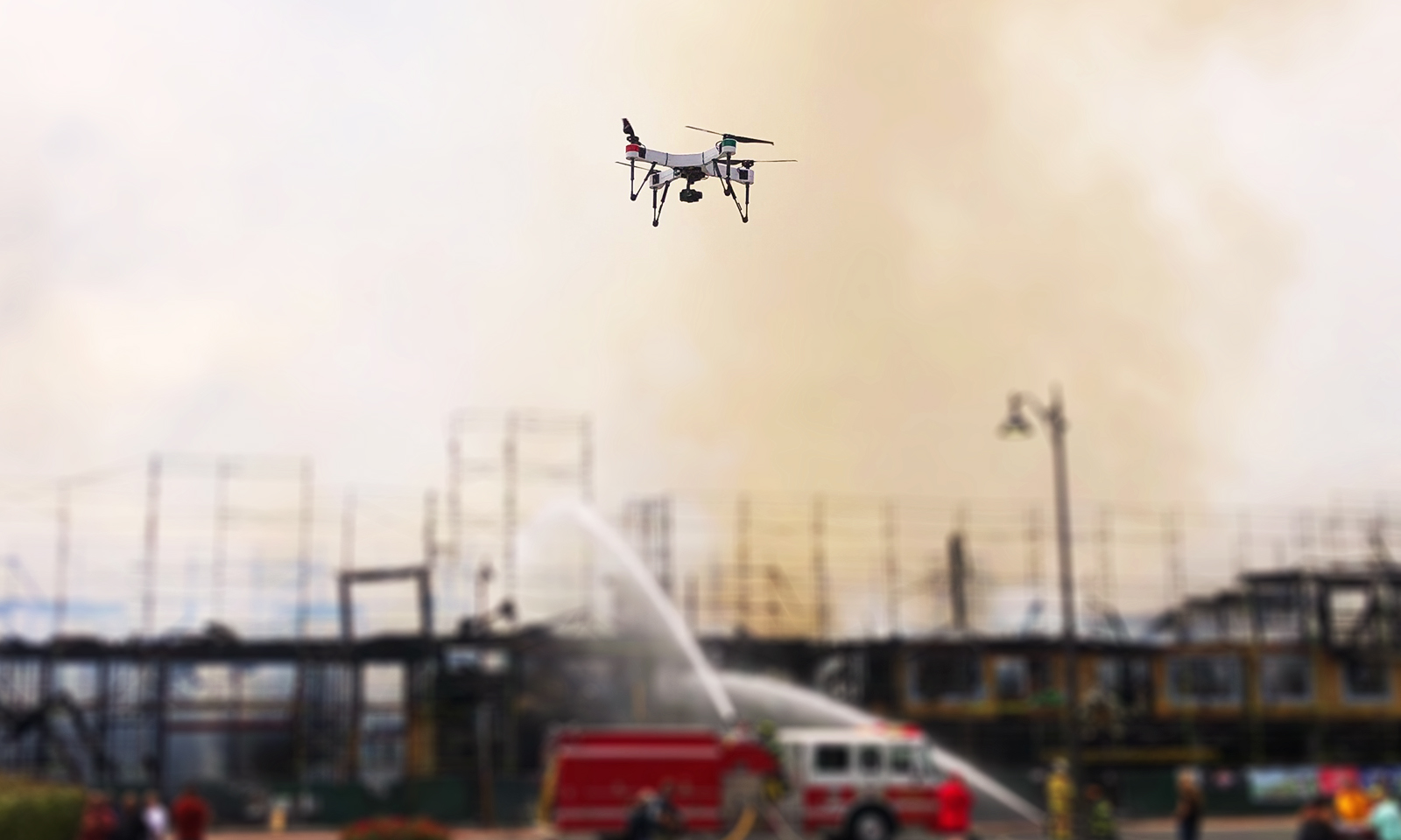 Drone flying in front of firefighters extinguishing a building fire