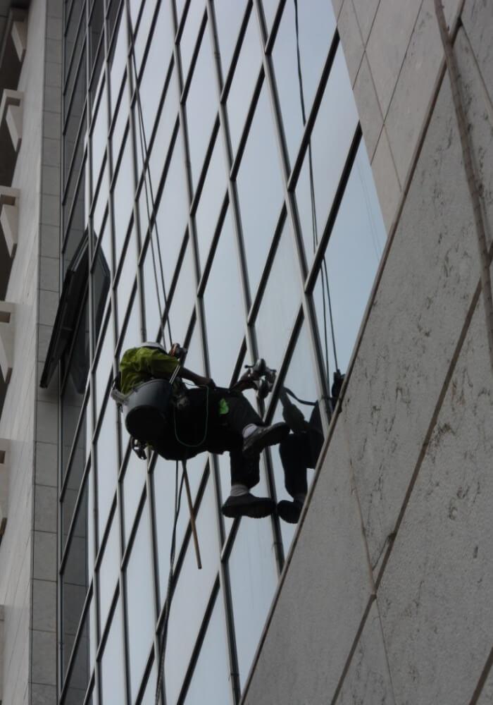 Técnico da Portal Vertical a fazer a limpeza dos vidros de um edifício preso por uma corda.