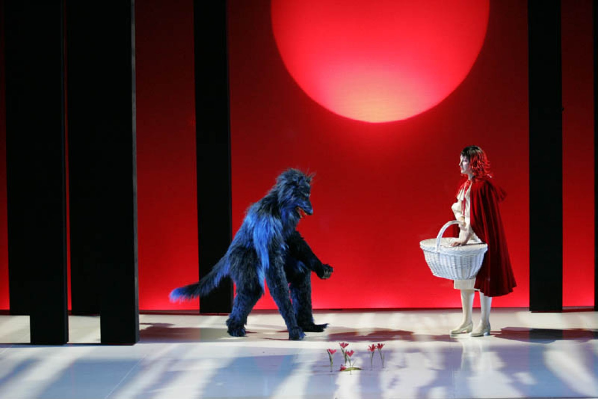 Blue-haired wolf confronts girl in red cloak carrying white wicker basket, on white stage in front of red sky and sun.