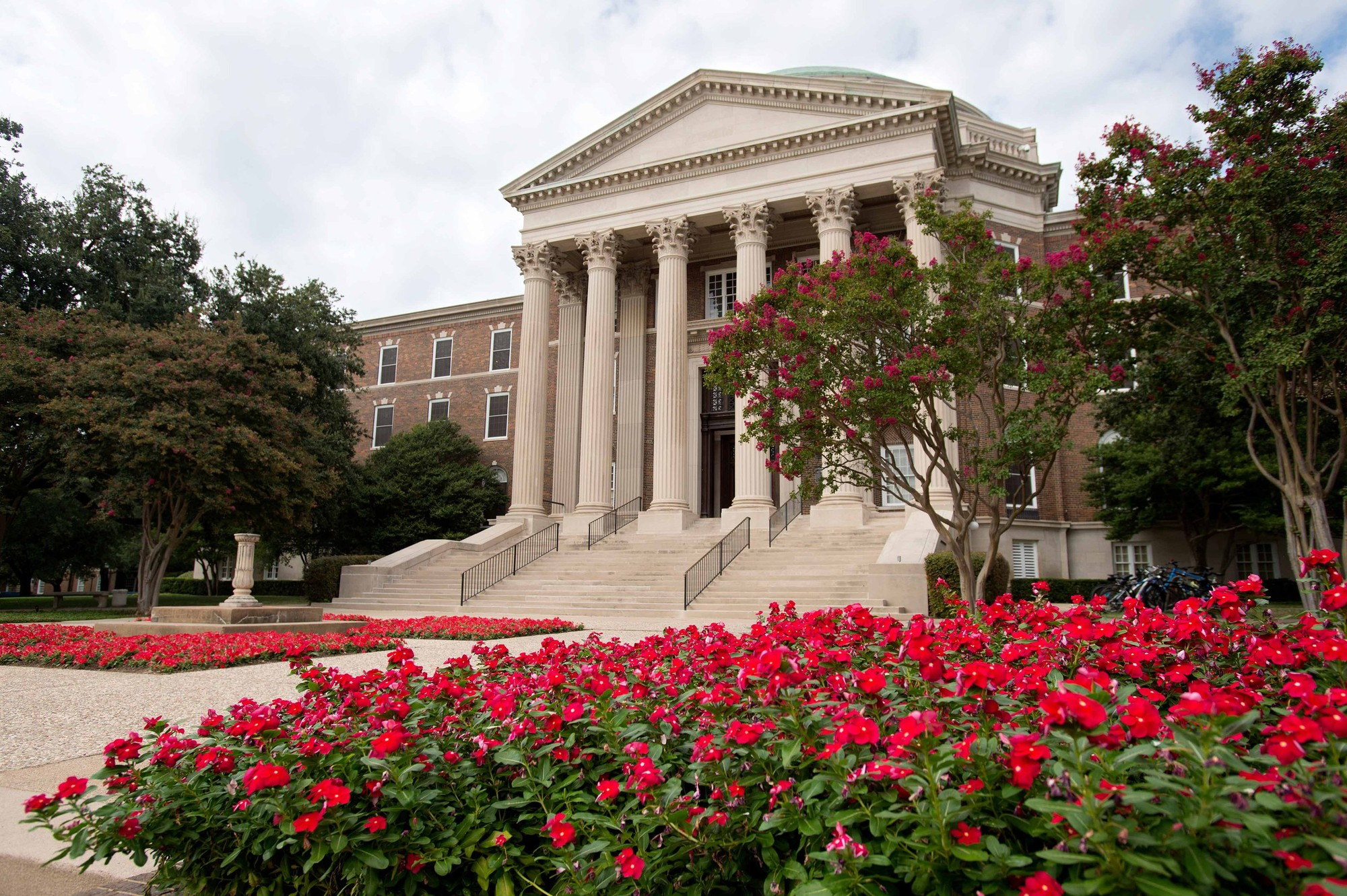 A view from the side of the stairs walkway lined with red flowering plants to Dallas Hall at SMU