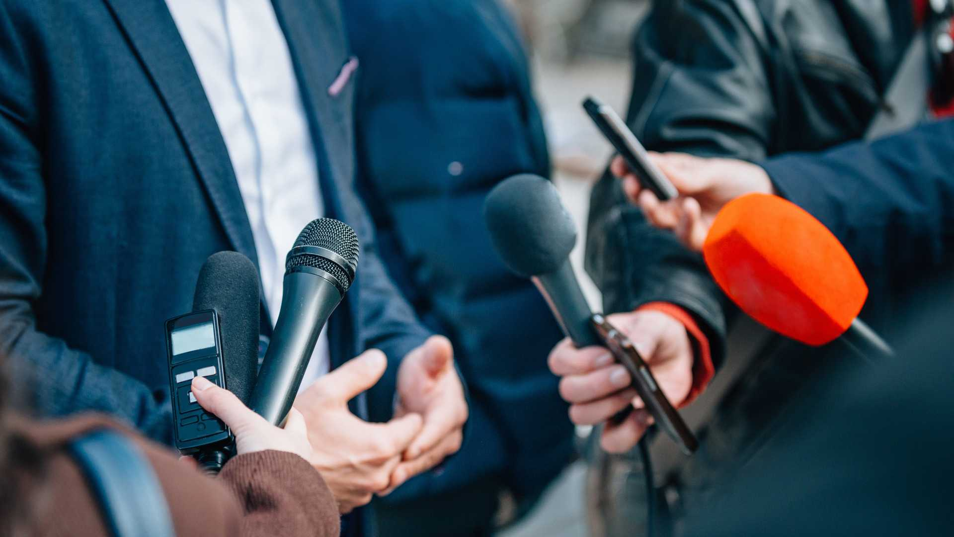 Business man speaking to reporters close up on microphones and hands