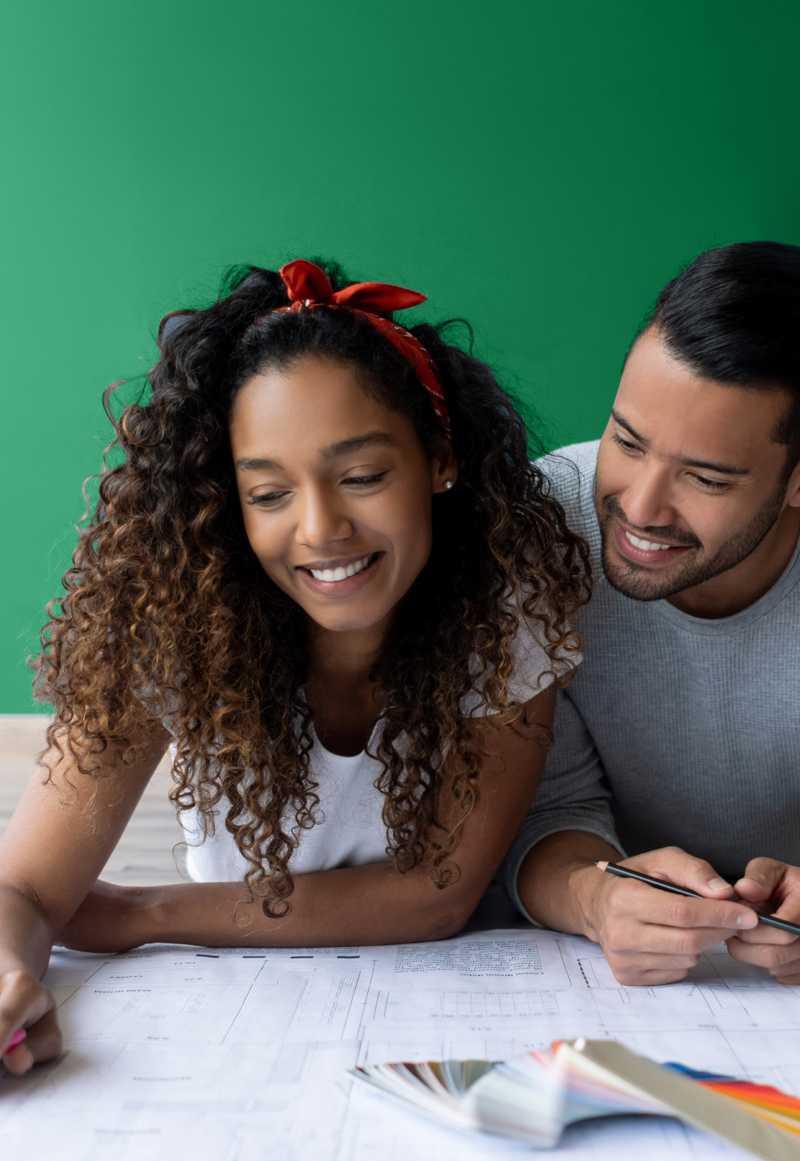 Imagem de uma mulher e um homem, planejando a reforma do seu imóvel, sorrindo.
