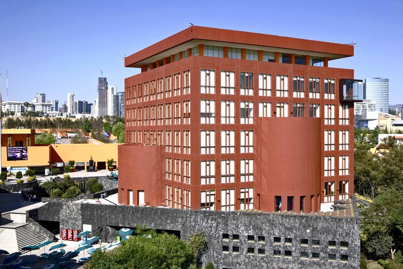 A reddish brown building on the EGADE Business School campus with other Monterrey buildings in the background