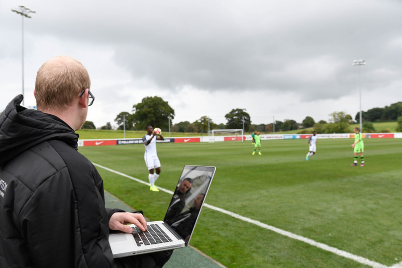 Man analyses soccer from sidelines