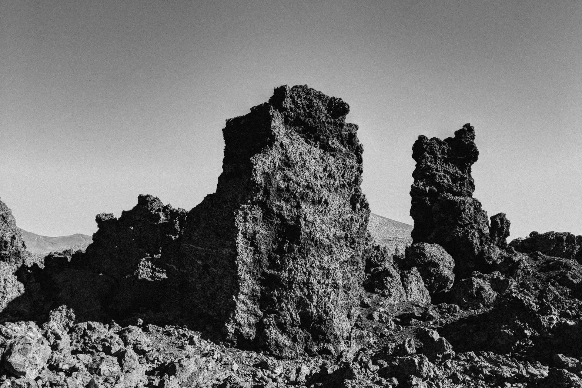 Three distinctive rock pillars rise out of a jagged lava field.