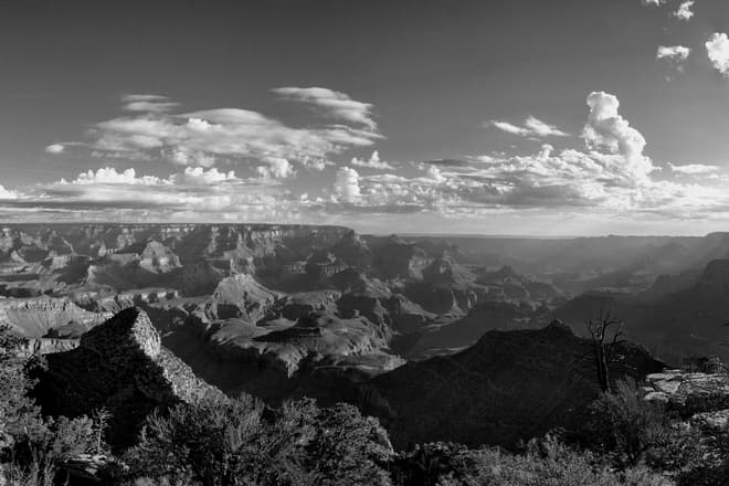 A black-and-white photograph of the Grand Canyon shortly after dawn.