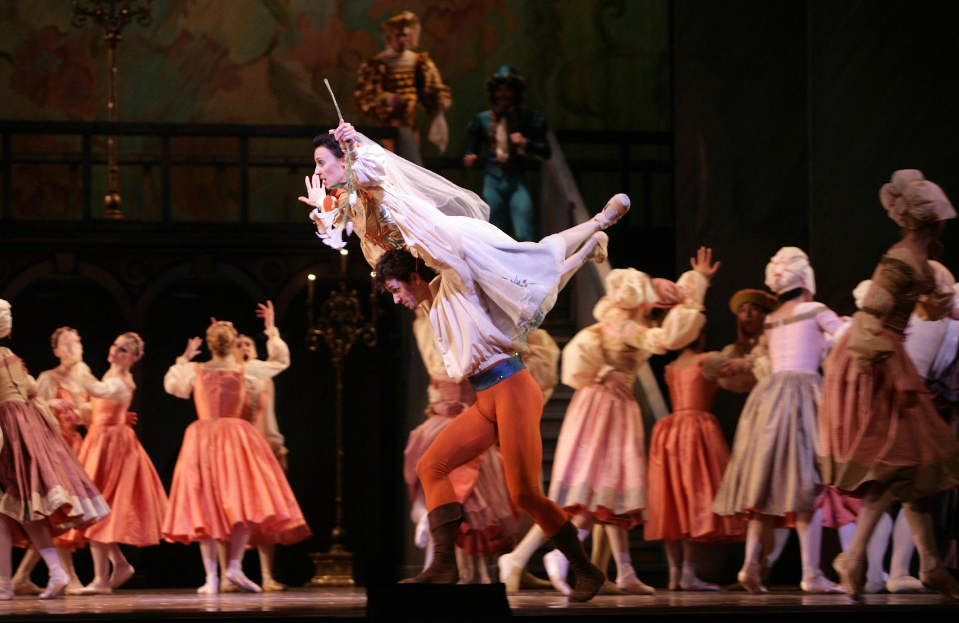 Ballerina in gauzy wedding dress is held aloft by dancer in orange tights amid crowd of blurry guests.