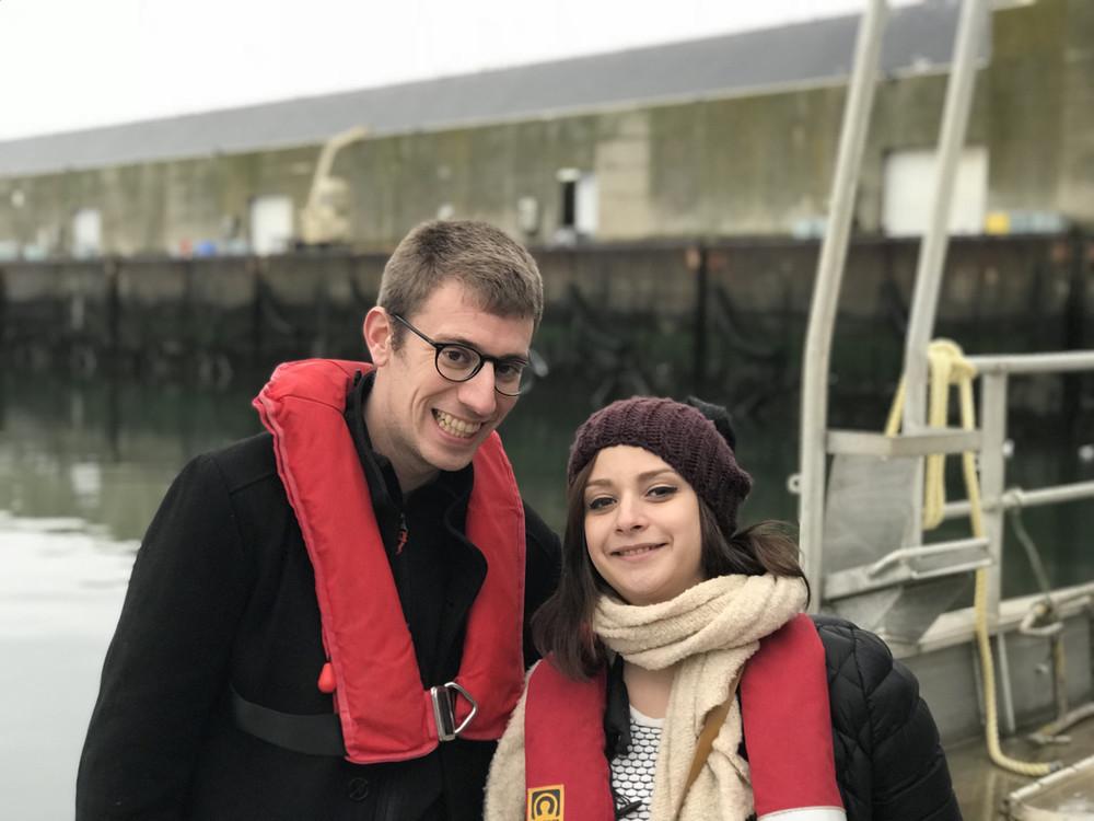 Antoine pose avec Elsa devant un port. Lui porte un manteau noir et un gilet de sauvetage rouge. Elle porte une doudoune noire, une grosse écharpe écrue, un bonnet et un gilet de sauvetage rouge.