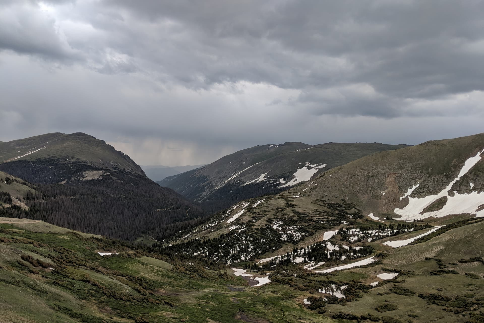 An alpine valley. The sky is gray with low clouds, and rain obscures what lies beyond the valley.