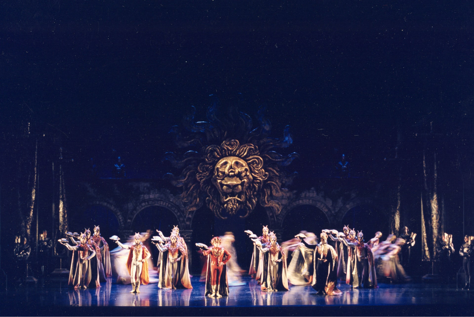 Lines of servants dance holding platters aloft on shiny stage in front of darkened bridge and lion's head statue.