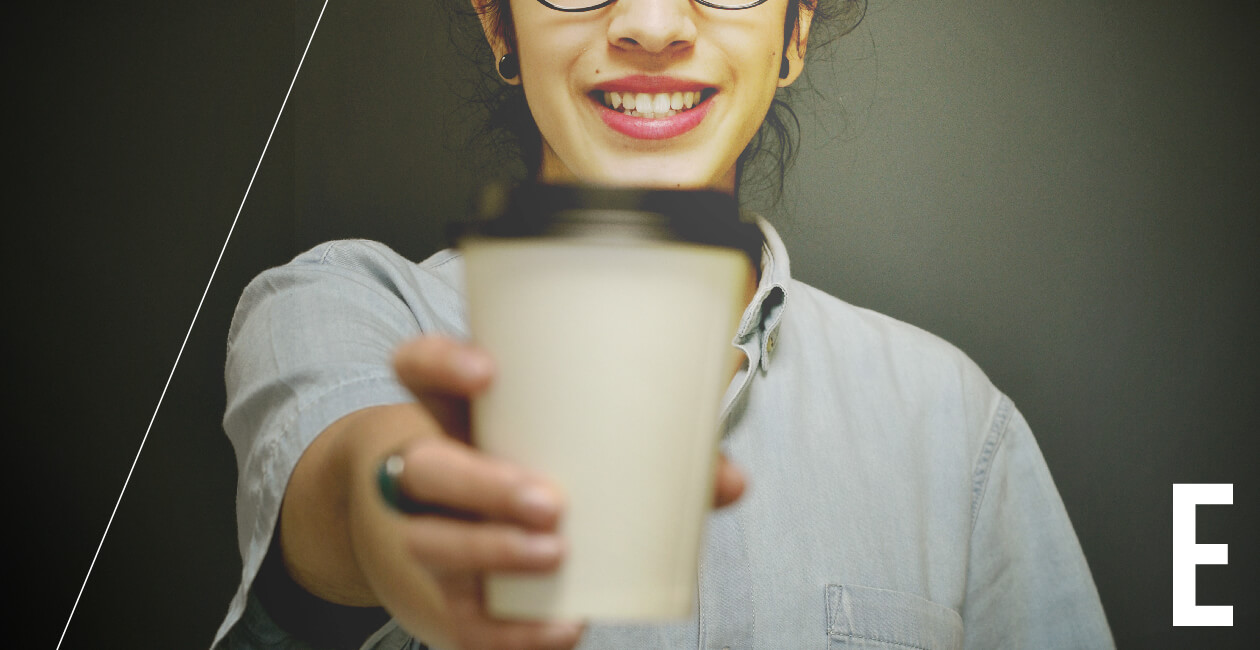 Empathetic woman UX designer holding a cup of coffee out to the camera and smiling
