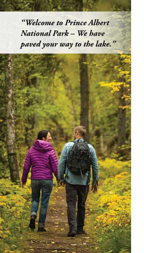 Two people walking on a dirt path in a forest. One is wearing a winter coat, and the other is wearing a backpack