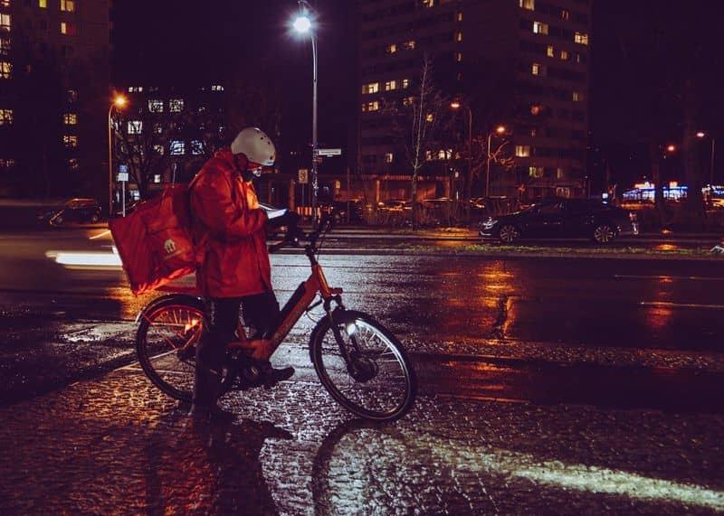 Ein Kurier, der Essen mit einem Rad ausliefert und auf sein Handy schaut