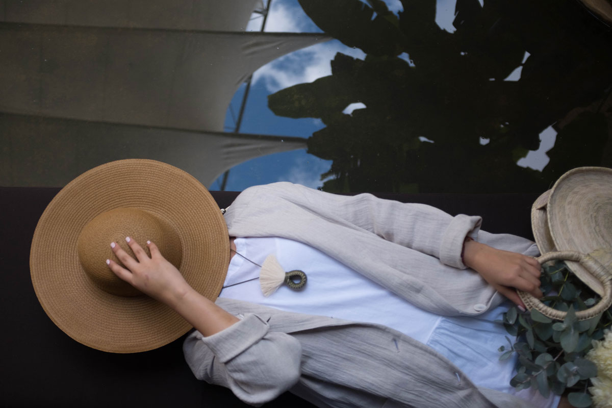 Aerial view of woman napping with hat over face