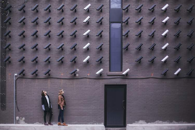 Image of security cameras pointed at two individuals