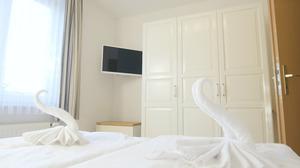 Andere Schlafzimmersicht mit Fernseher und großem Schrank