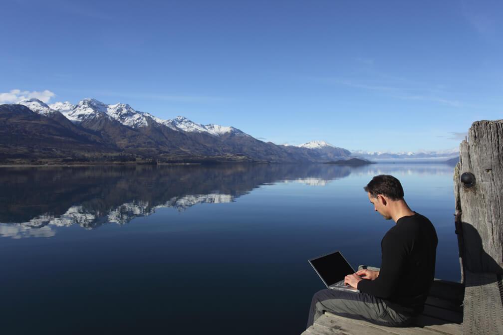 Um homem sentado a beira de um lago com várias montanhas com picos congelados a frente