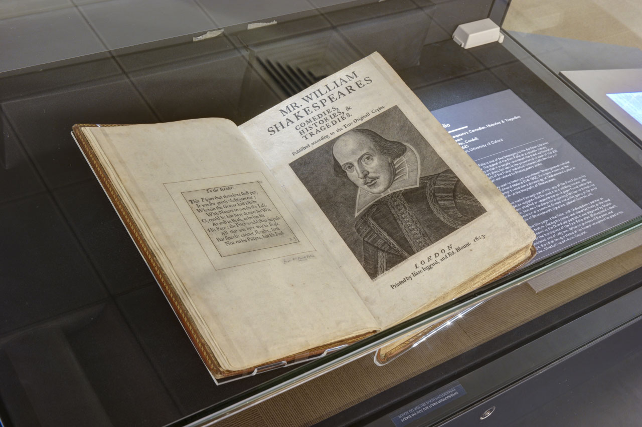 A photo showing the First Folio. The folio is opened up to a black and white etching of Shakesphere's portrait.