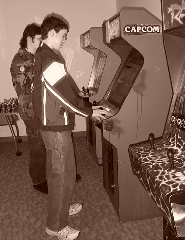 ANO members playing Arcade machines in monochrome.