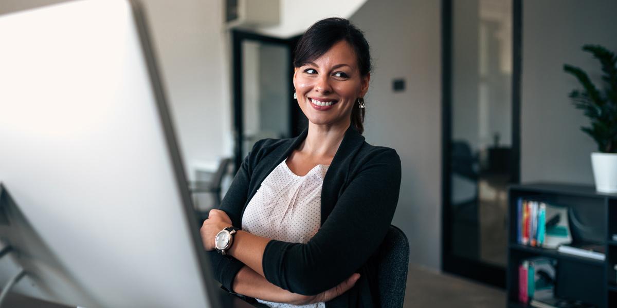 Designer sitting at her desk, smiling.