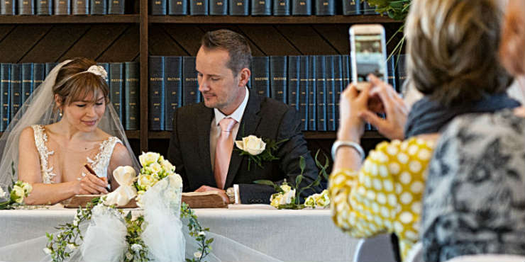 A wedding in a room lined with books