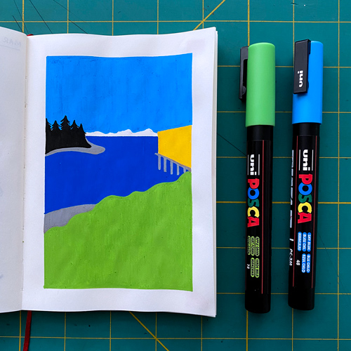 A blank notebook with a paint pen drawing of a bay with mountains behind it. Green and blue paint pens are laid next to the notebook.