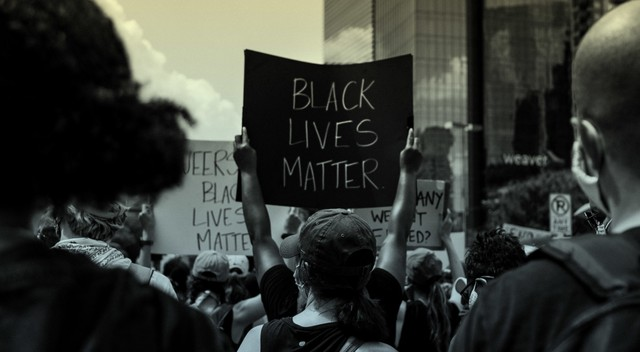 A group of people holds anti-racism signs at a Black Lives Matter protest