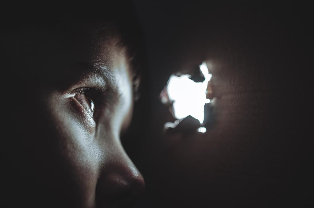 Boy looking through hole in wall: light shining through