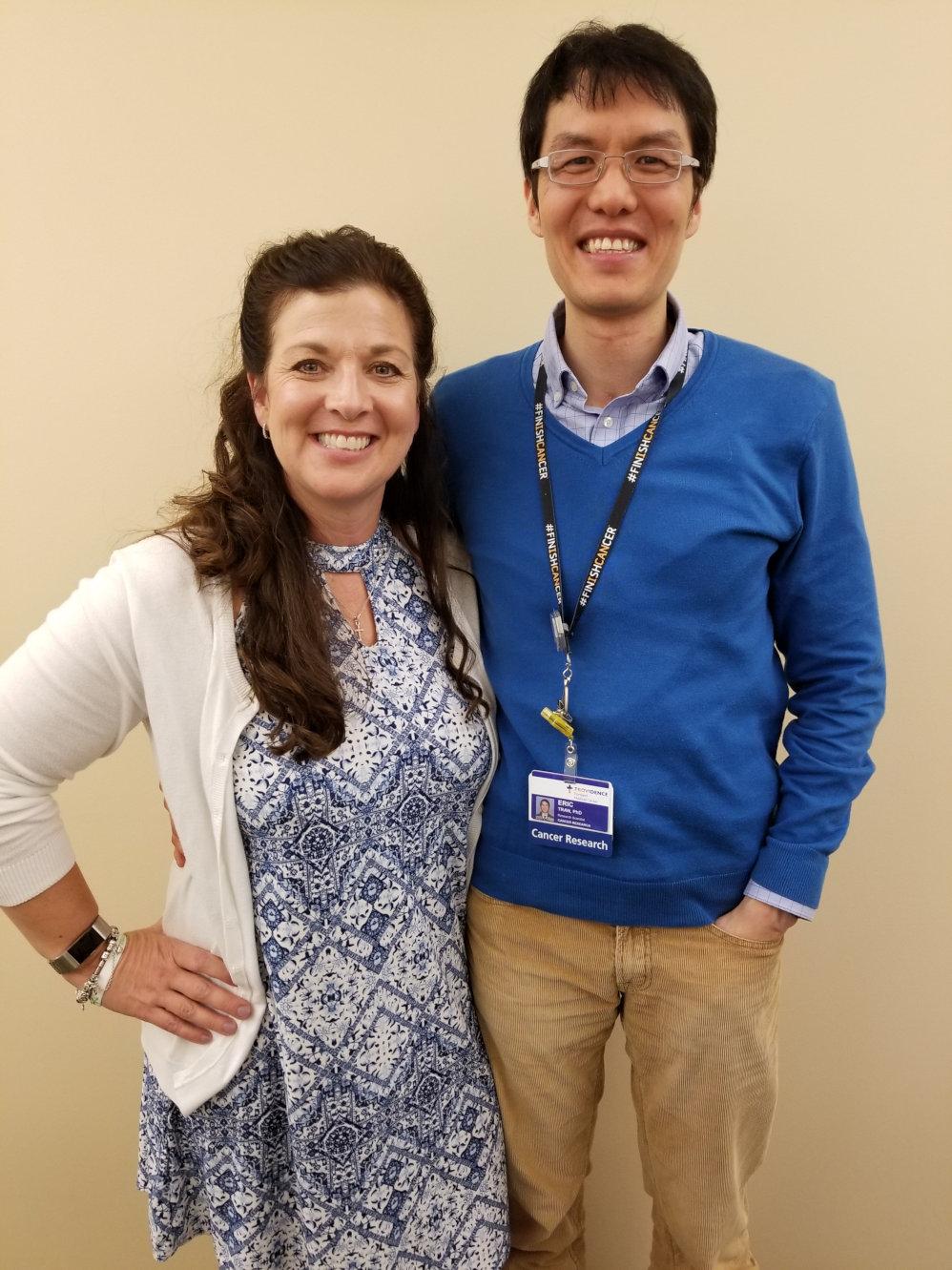 Melinda standing next to her doctor Eric Tran, both smiling