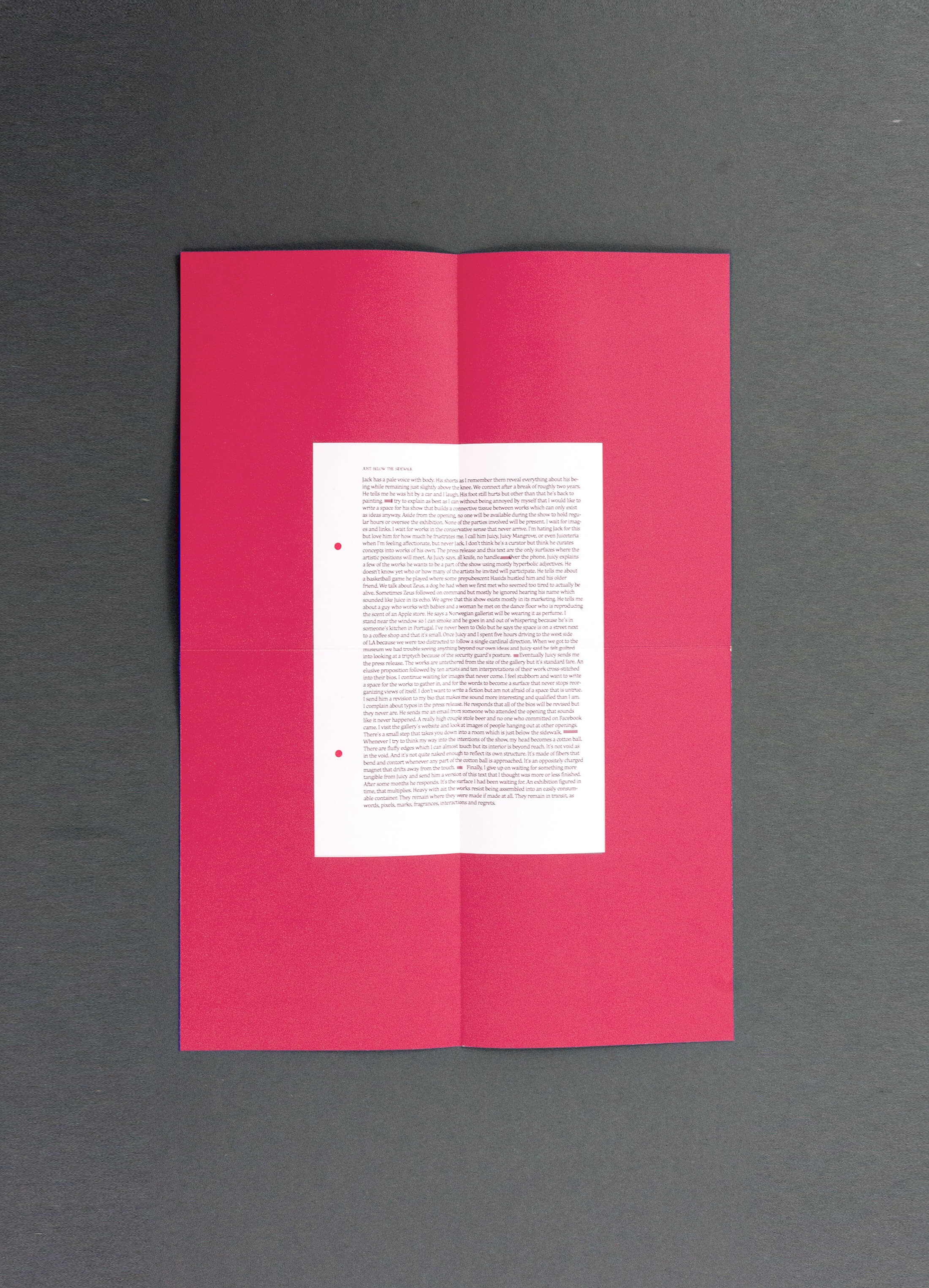 Folded piece of magenta paper with text on printed on it.