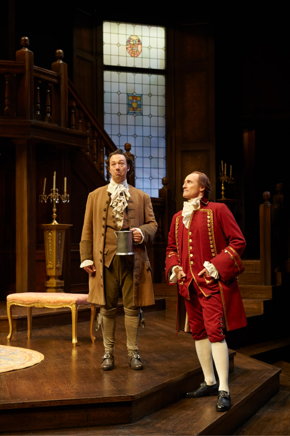 Red-suited man stands on step with perplexed man servant.