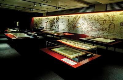 Several table showcases featuring maps are in a room, with a giant map graphic on the back wall.