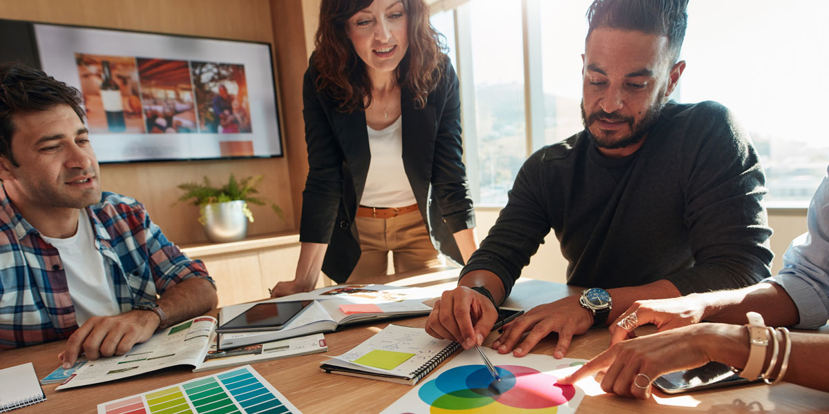 Group of four UI designers discuss the color palette during a business meeting