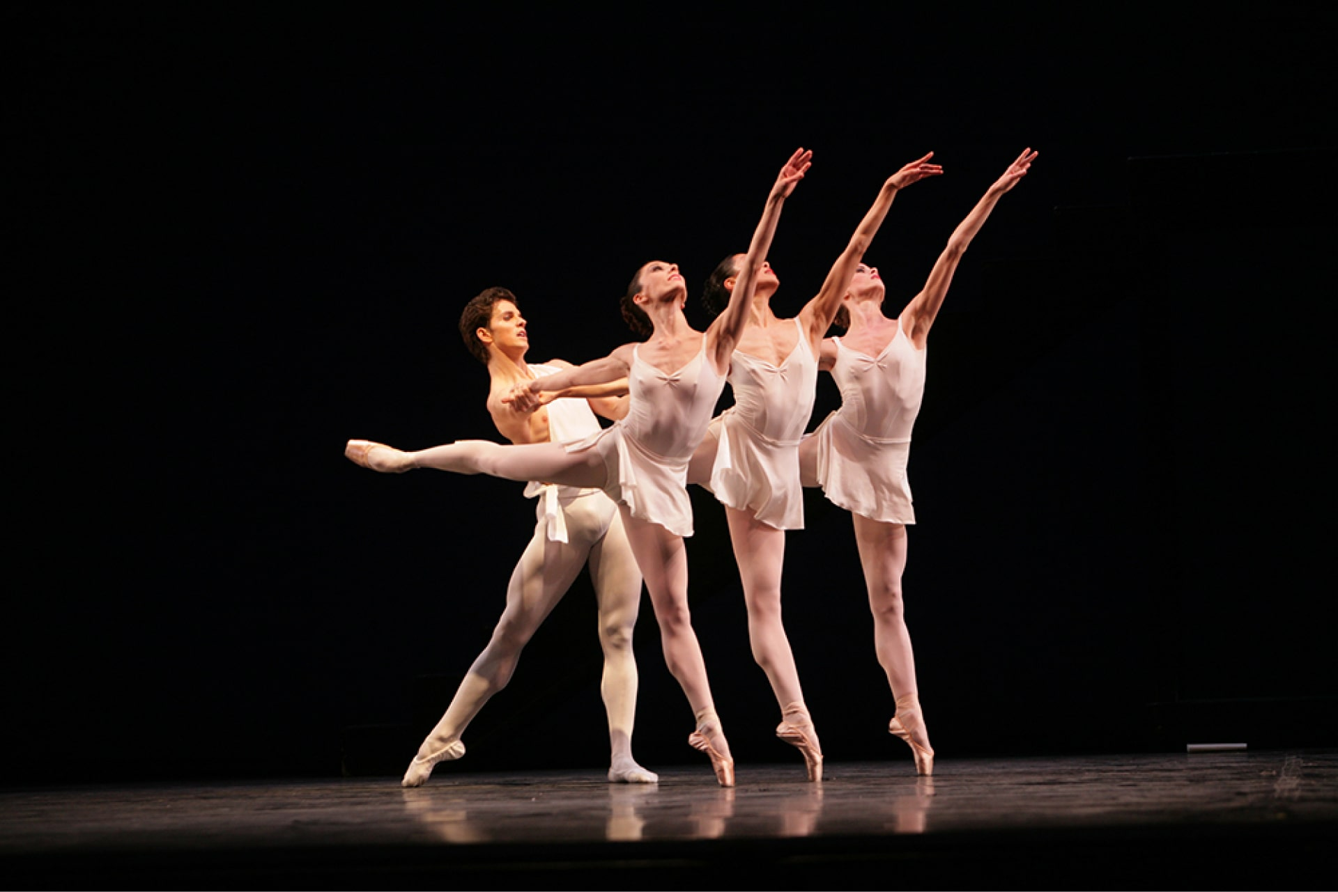 Bare-chested dancers hold hands of three ballerinas on point in arabesque.