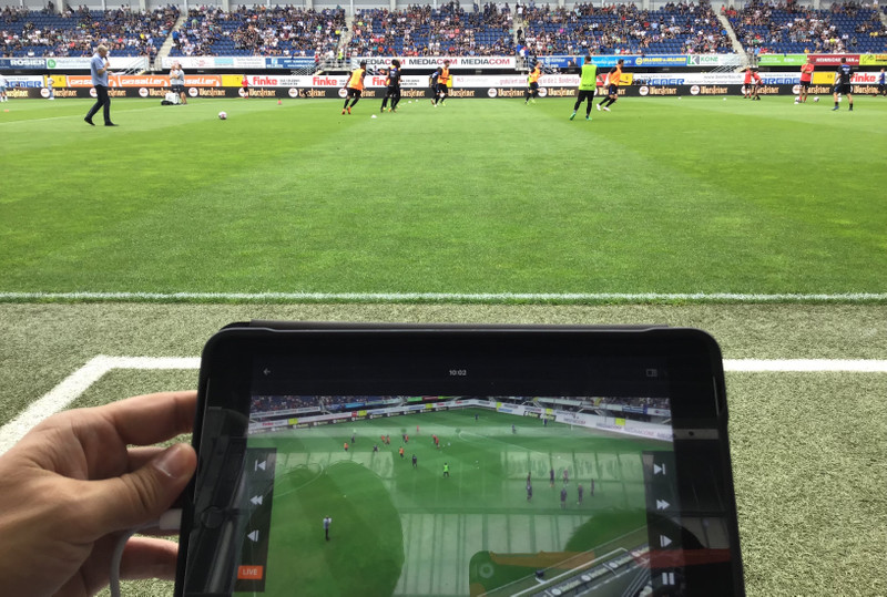 Manager watches live video on sidelines of football game