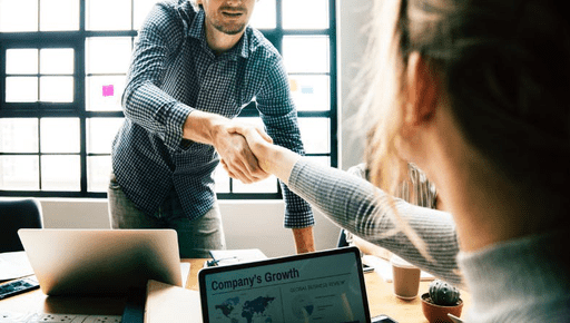 Colleagues shake hands across wooden desk with laptops, paper, notes and discuss to increase sales team thriving and prevent burnout as business owner and team colleagues #staff