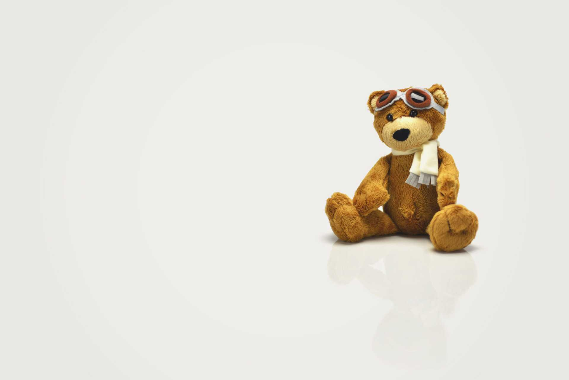 Brown teddy bear with goggles and a scarf on a white backgroud