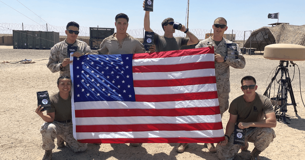 An image of deployed soldiers holding an American flag and items delivered from Soldiers' Angels