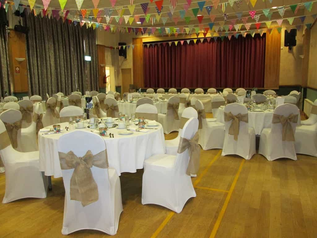 Happy simple event venue dressing with white and gold decor and rainbow flags hanging from ceiling