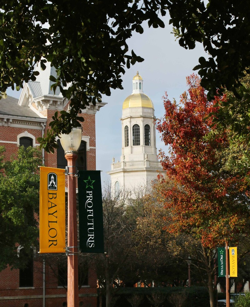 The gold steeple of Pat Neff Hall seen in the background of a Baylor University campus walkway