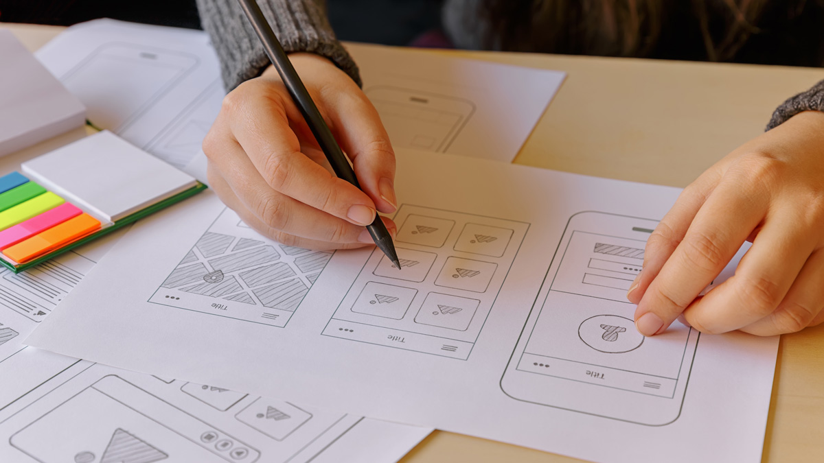 Close-up on a UX designer's hands, working on a set of paper prototypes