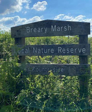 Breary Marsh entrance sign against a blue sky and grass