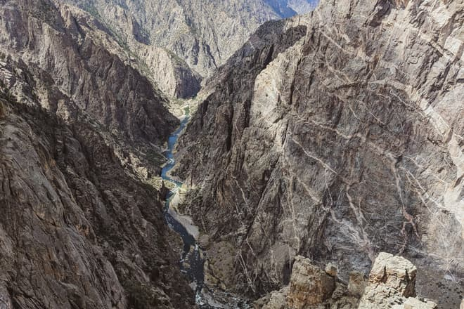 A view down the Gunnison, through the steep, broken walls of the Black Canyon. On the right, one of the dark purple canyon walls is shot through with intrusions of white granite.