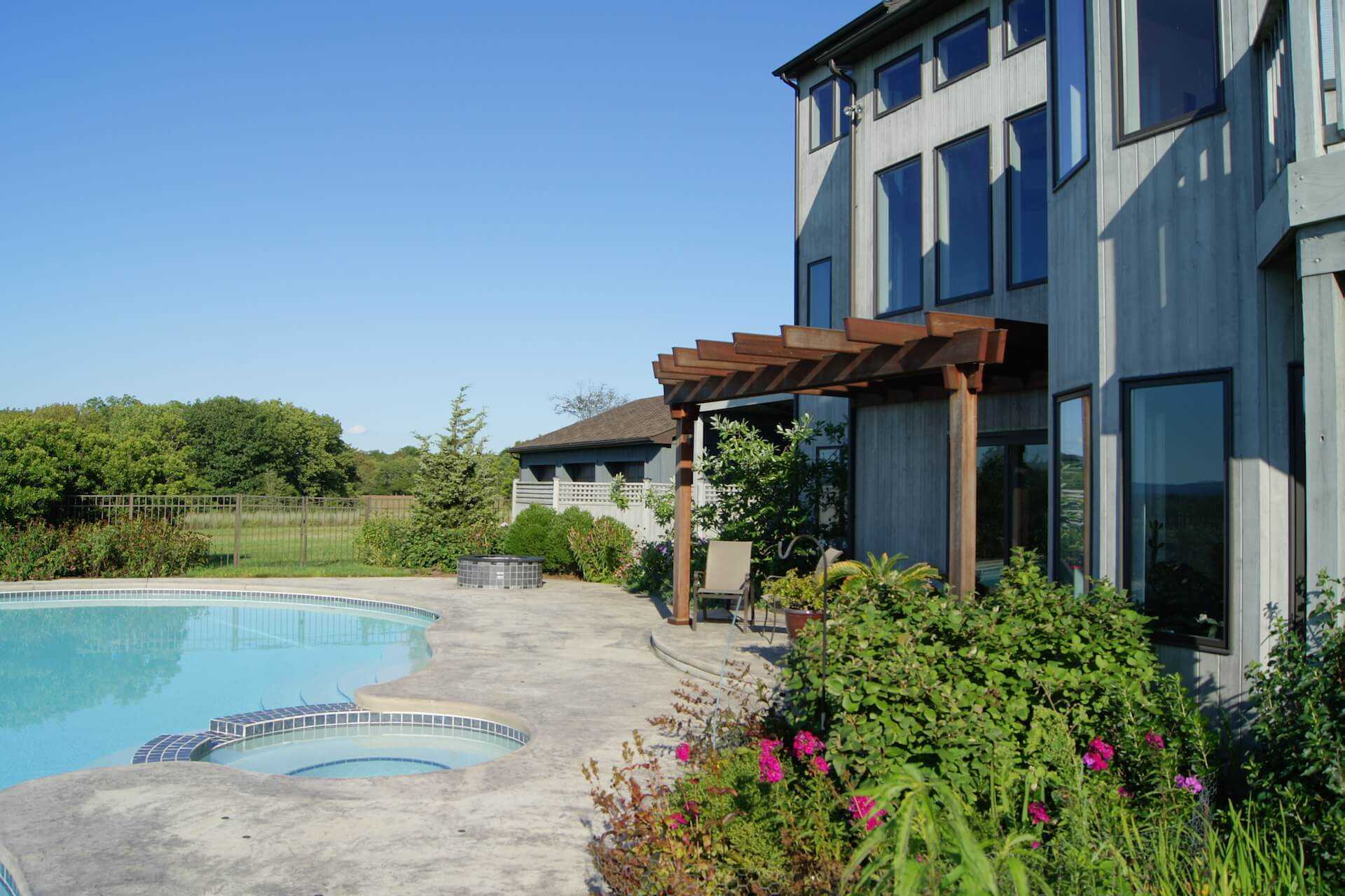 facing house  over flower planter to the right, and pool to the left